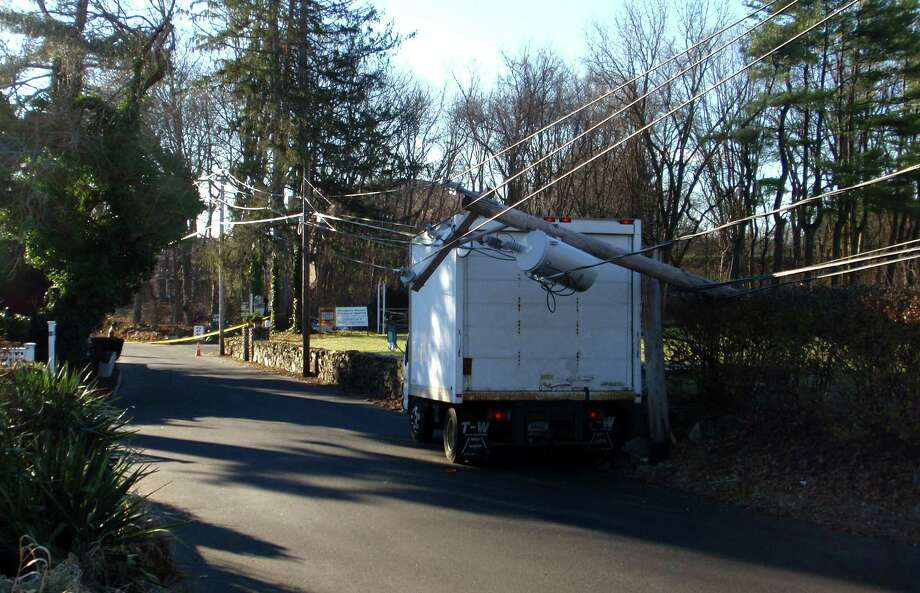 A box truck struck a utility pole on Sylvan Road South early Saturday, snapping off the pole and bringing down utility wires. Police shut down the road until about 6 p.m. Photo: Westport Fire Department / Westport News