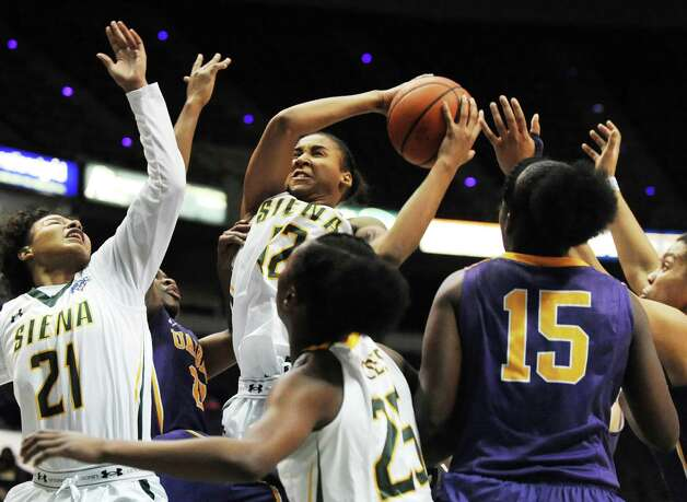 Siena's Symone Kelly, center, grabs the rebound during their basketball game against UAlbany on Saturday Dec. 13, 2014, at Times Union Center in Albany, N.Y. (Cindy Schultz / Times Union) Photo: Cindy Schultz / 00029815A