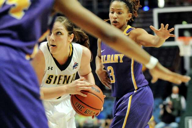 Siena's Margot Hetzke, center, works the paint as UAlbany's Margarita Rosario defends during their basketball game on Saturday Dec. 13, 2014, at Times Union Center in Albany, N.Y. (Cindy Schultz / Times Union) Photo: Cindy Schultz / 00029815A