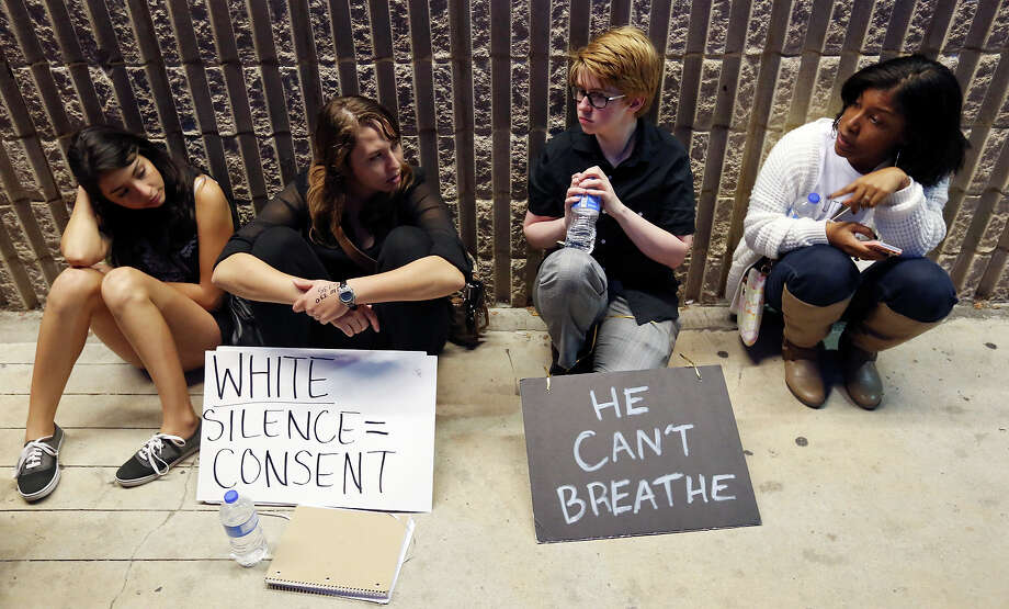 Protesters Viktoria Zerda, 21, (from left), Bela Kriger, 21, Andy Brown, 23, and Isha Clayton, 26, wait outside the Magistrate and Detention Center Saturday Dec. 13, 2014 after two members of the group SATX4 were arrested near North Star Mall. Photo: Edward A. Ornelas, San Antonio Express-News / © 2014 San Antonio Express-News