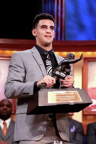 NEW YORK, NY - DECEMBER 13:  Marcus Mariota, quarterback for the University of Oregon Ducks, hoist the trophy after being named the 80th Heisman Memorial Trophy Award winner during the 2014 Heisman Trophy Presentation at the Best Buy Theater on December 13, 2014 in New York City.  NOTE TO USER FOR EDITORIAL USE ONLY: Photographer approval needed for all Commercial License requests.  (Photo by Kelly Kline - Handout/Getty Images for The Heisman) ORG XMIT: 526894097 Photo: Handout / 2014 The Heisman