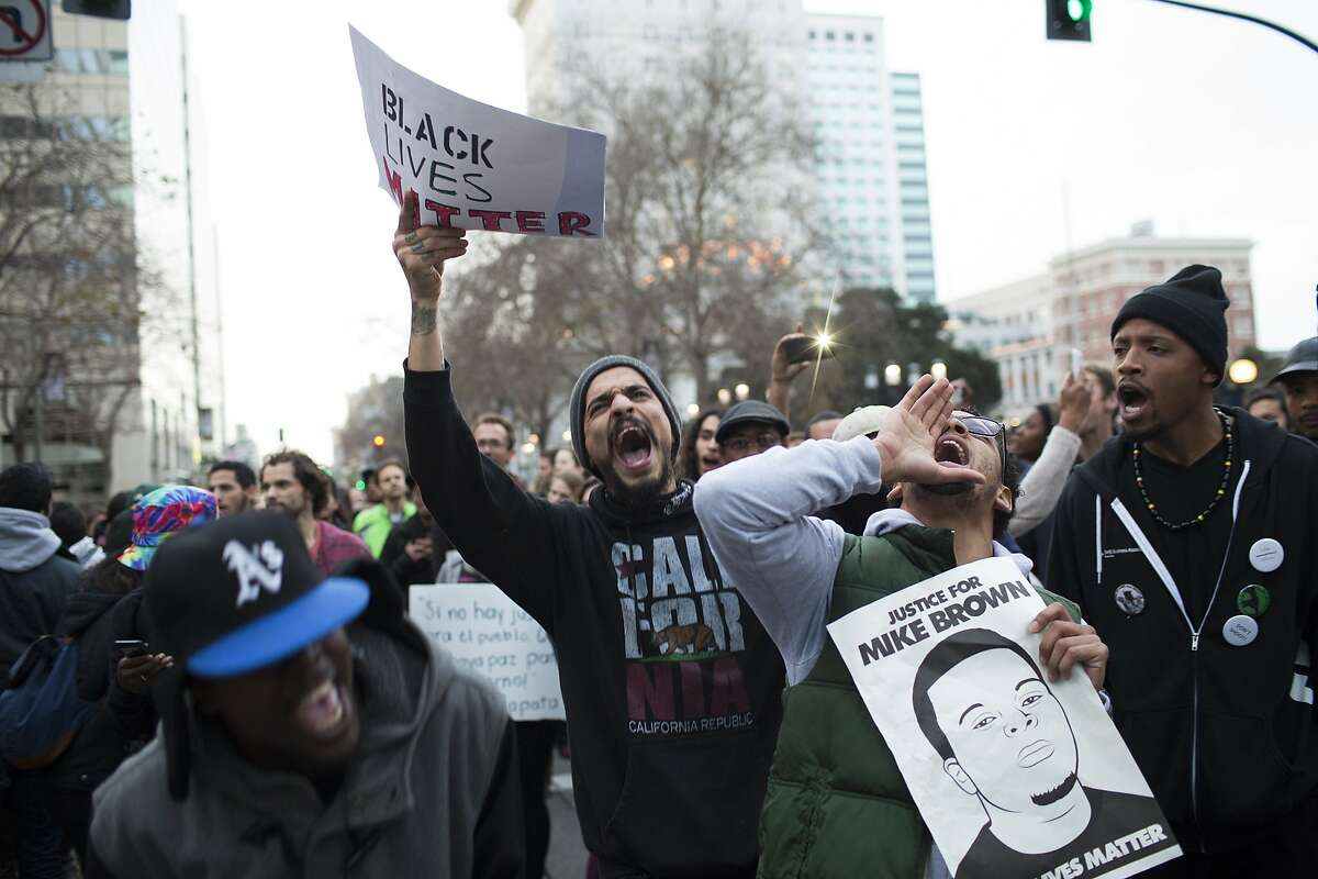 Tay Lewis, of Oakland, left, Carlos Valdovinos, center, of Berkeley, center, and Devon Weseley, right, chant during a �