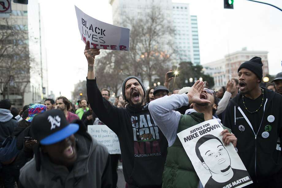 "Tay Lewis, of Oakland, left, Carlos Valdovinos, center, of Berkeley, center, and Devon Weseley, right, chant during a ""Day of Resistance"" or the ""Millions March"" in Oakland, Calif. on Saturday, December 13, 2014. Photo: Tim Hussin, Special To The Chronicle"