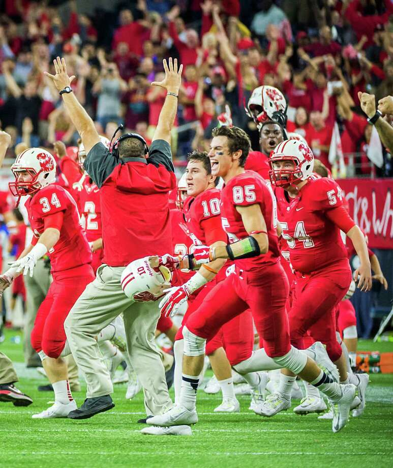 After the defense held Cibolo Steele scoreless on its overtime possession, the Katy players rush onto the field to celebrate a hard-earned victory Saturday. Photo: Smiley N. Pool, Staff / © 2014  Houston Chronicle