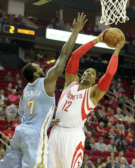 On the court for the first time since Nov. 17, Rockets center Dwight Howard (12) was an overwhelming presence against J.J. Hickson and the Nuggets. Photo: Thomas B. Shea / © 2014 Thomas B. Shea
