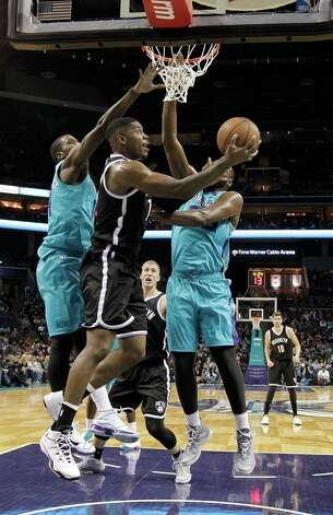 Brooklyn Nets' Joe Johnson, center, gets his shot off against Charlotte Hornets' Michael Kidd-Gilchrist, left, and Al Jefferson, right, during the first half of an NBA basketball game in Charlotte, N.C., Saturday, Dec. 13, 2014. (AP Photo/Bob Leverone) ORG XMIT: NCBL105 Photo: Bob Leverone / FR170480 AP
