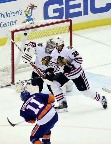 New York Islanders defenseman Lubomir Visnovsky (11) shoots the puck past Chicago Blackhawks goalie Scott Darling (33) to score as Blackhawks defenseman Michal Rozsival (32) looks on in the third period of an NHL hockey game at Nassau Coliseum on Saturday, Dec. 13, 2014, in Uniondale, N.Y. The Islanders won 3-2.  (AP Photo/Kathy Kmonicek) ORG XMIT: NYI112 Photo: Kathy Kmonicek / FR170189 AP