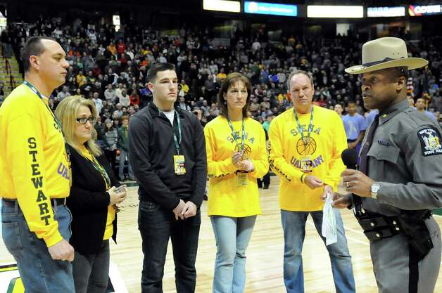 Troop G Commander Steven James, right, speaks during a ceremony to raise awareness about distracted driving prior to the UAlbany vs. Siena basketball game on Saturday Dec. 13, 2014, at Times Union Center in Albany, N.Y. From left are Brian Rivers and Debbie Rivers, parents of Deanna Rivers, Matt Hardy and Regina Stewart and Michael Stewart, parents of Christopher Stewart. (Cindy Schultz / Times Union) Photo: Cindy Schultz / 00029844A