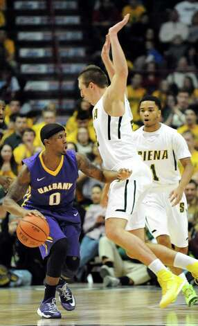 UAlbany's Evan Singletary, left, controls the ball as Siena's Willem Brandwijk, center, defends during their basketball game on Saturday Dec. 13, 2014, at Times Union Center in Albany, N.Y. (Cindy Schultz / Times Union) Photo: Cindy Schultz / 00029816A