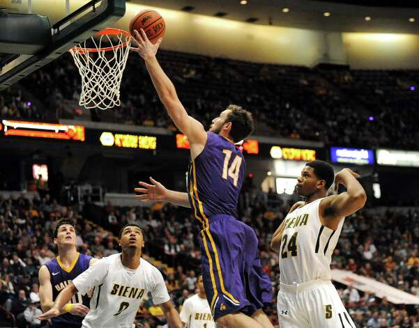UAlbany's Sam Rowley, center, shoots for the hoop during their basketball game against Siena on Saturday Dec. 13, 2014, at Times Union Center in Albany, N.Y. (Cindy Schultz / Times Union) Photo: Cindy Schultz / 00029816A