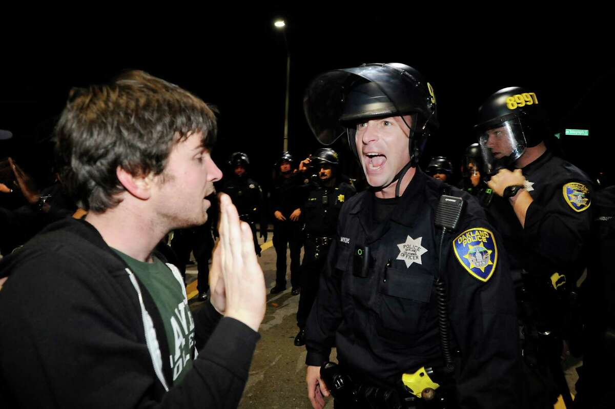 An officer yells at protesters that are kettled on the corner of Telegraph and 29th St. as anti-police brutality protests continue in Oakland on Saturday in the wake of the Michael Brown ruling in Missouri and the Eric Garner ruling in New York.