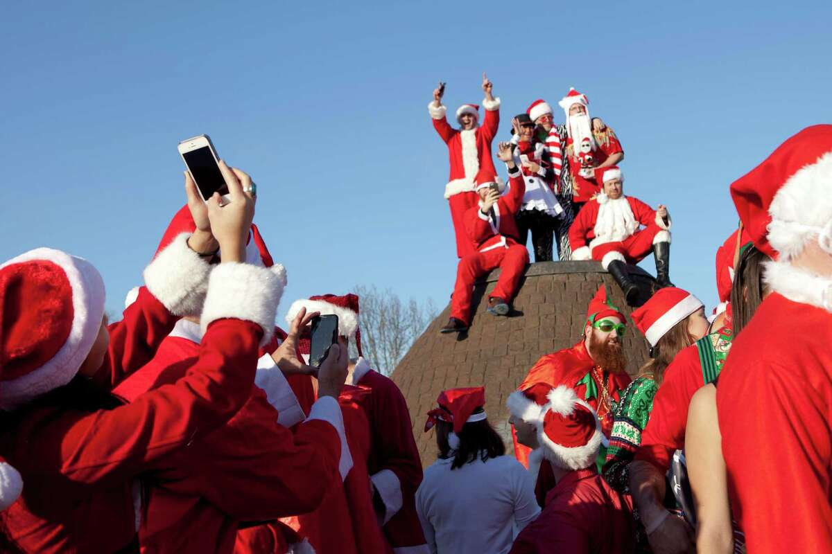 A group of Santa's gathered together at Cal Anderson Park during a pub crawl on Capitol Hill in the early afternoon on Saturday, Dec. 13, 2014, in Seattle.
