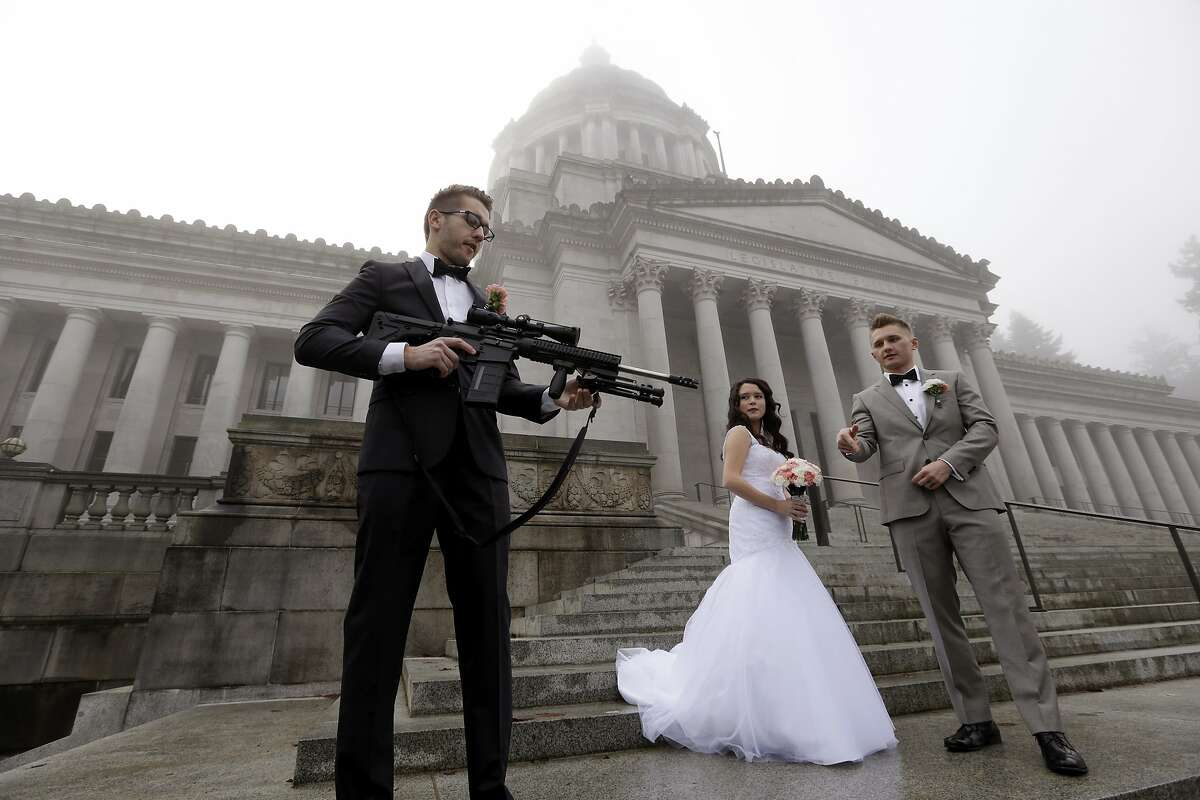 The best man in a wedding party, who all declined to be identified, holds an AR-10 rifle he was handed while the party was having their pre-wedding portraits taken on the steps of the capitol before a rally nearby by gun-rights advocates to protest a new expanded gun background check law in Washington state Saturday, Dec. 13, 2014, in Olympia, Wash. The wedding party was not part of the protest, but posed for pictures with it after being handed it by gun activist Brandon Lyons, who said