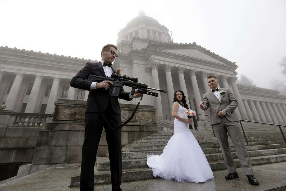 "The best man in a wedding party, who all declined to be identified, holds an AR-10 rifle he was handed while the party was having their pre-wedding portraits taken on the steps of the capitol before a rally nearby by gun-rights advocates to protest a new expanded gun background check law in Washington state Saturday, Dec. 13, 2014, in Olympia, Wash. The wedding party was not part of the protest, but posed for pictures with it after being handed it by gun activist Brandon Lyons, who said ""we've all just broken the law,"" by handing the gun over. Saturday's protest was called the ""I Will Not Comply"" rally, and those attending said they will openly exchange firearms in opposition to the state's new voter-approved universal background check law, Initiative 594. The law, which took effect on Dec. 4, requires background checks on all sales and transfers, including private transactions and many loans and gifts. (AP Photo/Elaine Thompson) Photo: Elaine Thompson, Associated Press"