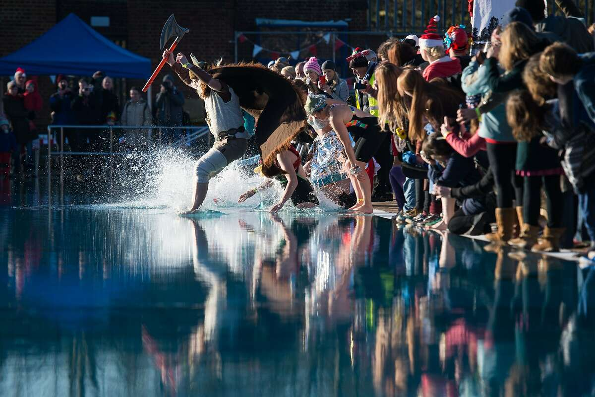 MAY THE NORSE BE WITH YOU: An ax-wielding Viking leads the group plunge during the Outdoor Swimming Society's annual