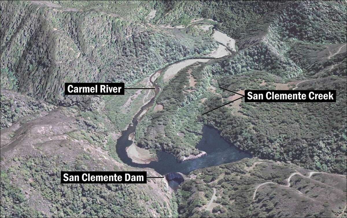 An aerial view of the San Clemente Dam, with the Carmel River and San Clemente Creek flowing into the silted over reservoir.