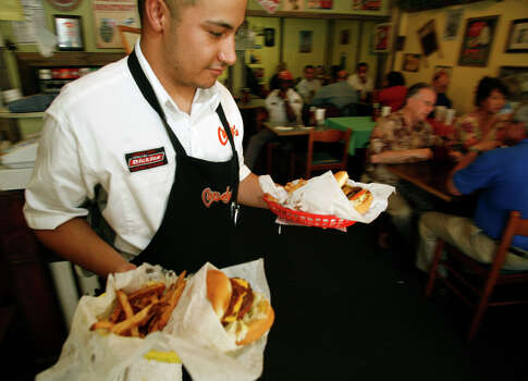 A look at the lunch scene at Candy's Old Fashion Burgers on S.Flores in San Antonio, where Mark Velasquez brings out an order, Friday, July 10, 2009. ( Photo by J. Michael Short / SPECIAL ) Photo: J. MICHAEL SHORT, Express-News File Photo / 210SA