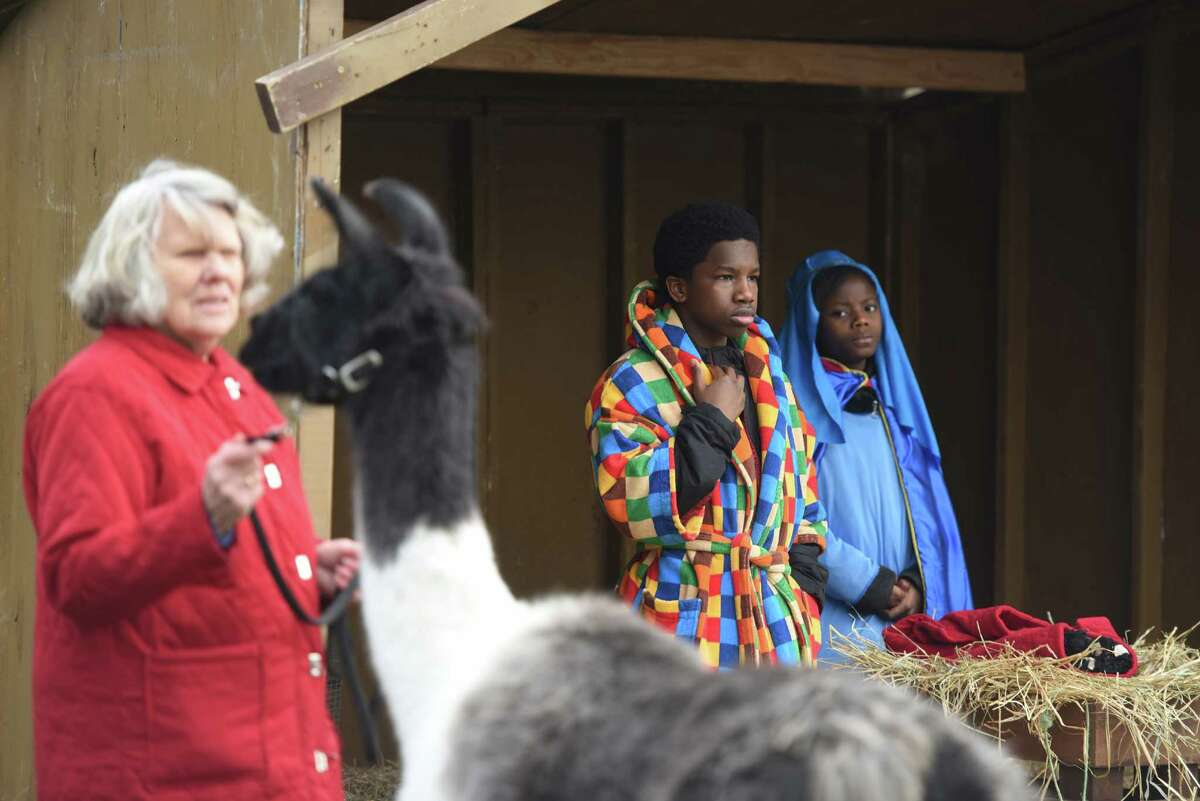 Wanda Williams and her llama stand outside a stable as Frankeda Fawundu, 11, and Sebastian Pierre-Louis, 11, portray Mary and Joseph during the live nativity at First United Methodist Church in Stamford, Conn. Sunday, Dec. 14, 2014. Children dressed up and portrayed Mary, Joesph and others from the Bible, with live animals, as a large group watched and sang Christmas carols.