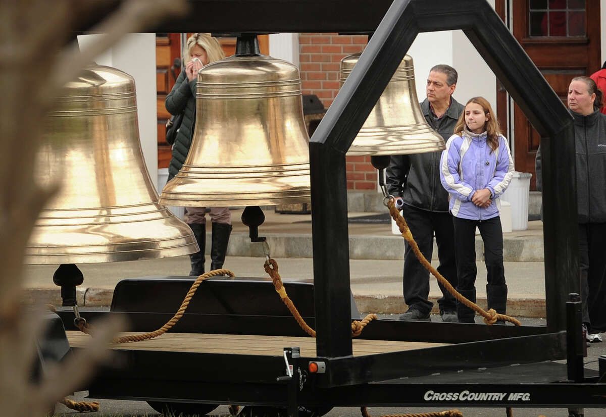 Parishioners emerge from mass at St. Rose of Lima Catholic Church to ring a series of bells on the second anniversary of the Sandy Hook Elementary School killings in Newtown, Conn. on Sunday, December 14, 2014. Gov. Malloy attended the service.