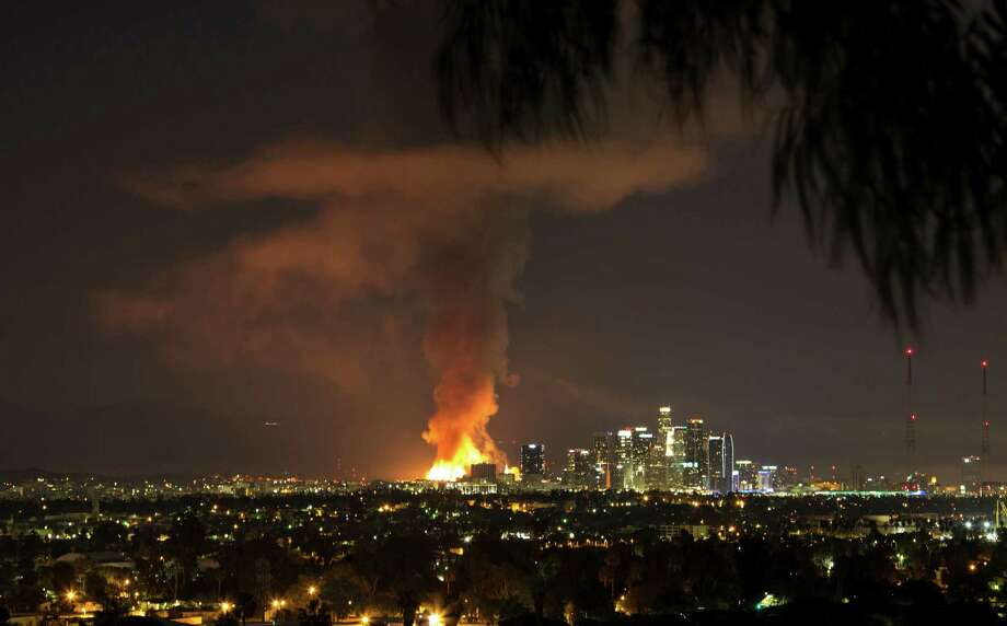 This photo provided by Nancy Yuille shows a massive fire engulfing an apartment building construction site near downtown Los Angeles on Monday, Dec. 8, 2014. Crews battled two large fires in Los Angeles early Monday, including a massive one downtown that closed portions of two major freeways and blanketed the area in ash and heavy smoke.Latest from AP: Feds aid probe of Los Angeles apartment blaze Photo: Nancy Yuille, AP / Nancy Yuille