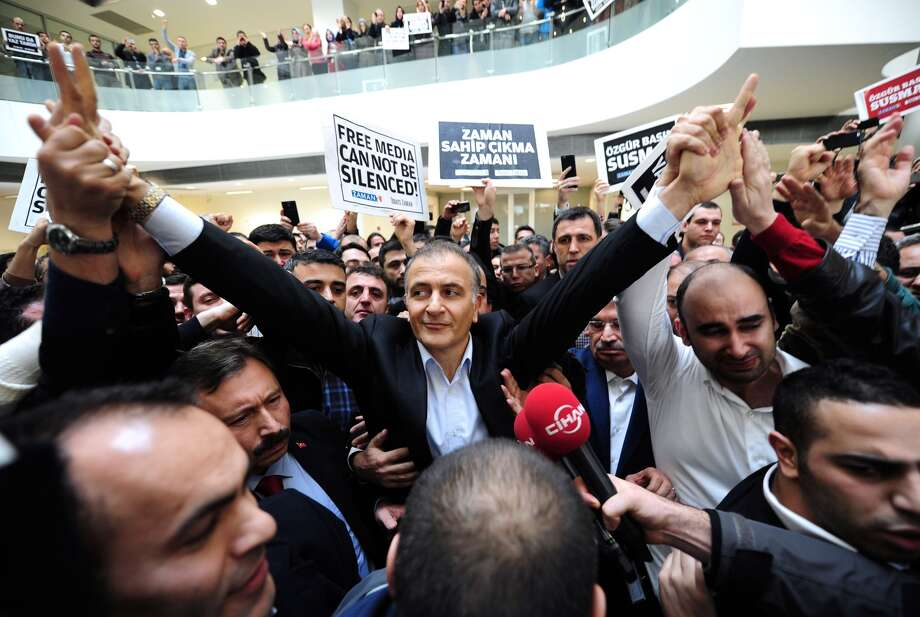 Ekrem Dumanli (center), editor-in-chief of   Zaman , Turkey's top-selling newspaper, waves to staff members, while being arrested by counterterror police at the newspaper's headquarters in Istanbul. Photo: OZAN KOSE / AFP/Getty Images / AFP
