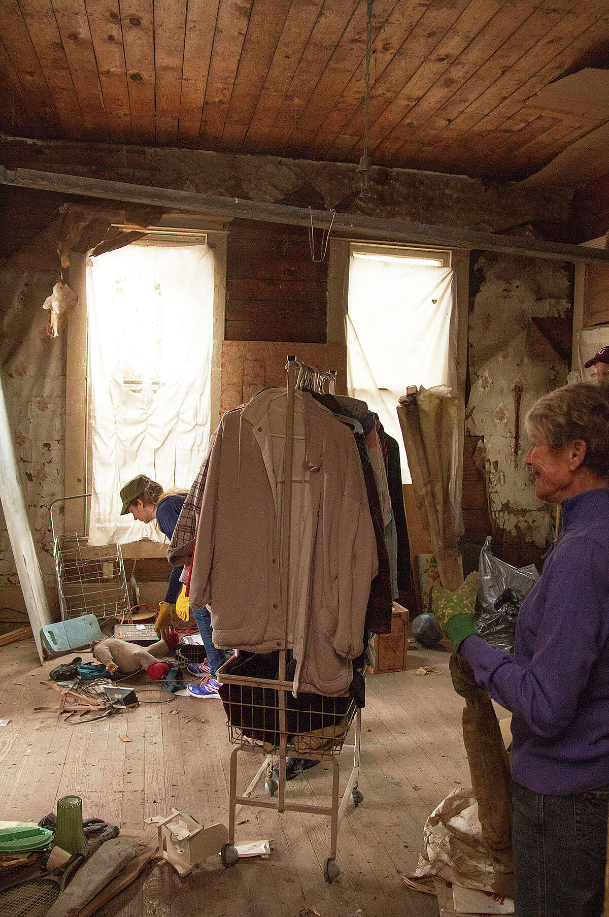 Volunteers help clean out Miguel Calzada's home for renovations, Saturday, Dec. 13, 2014.