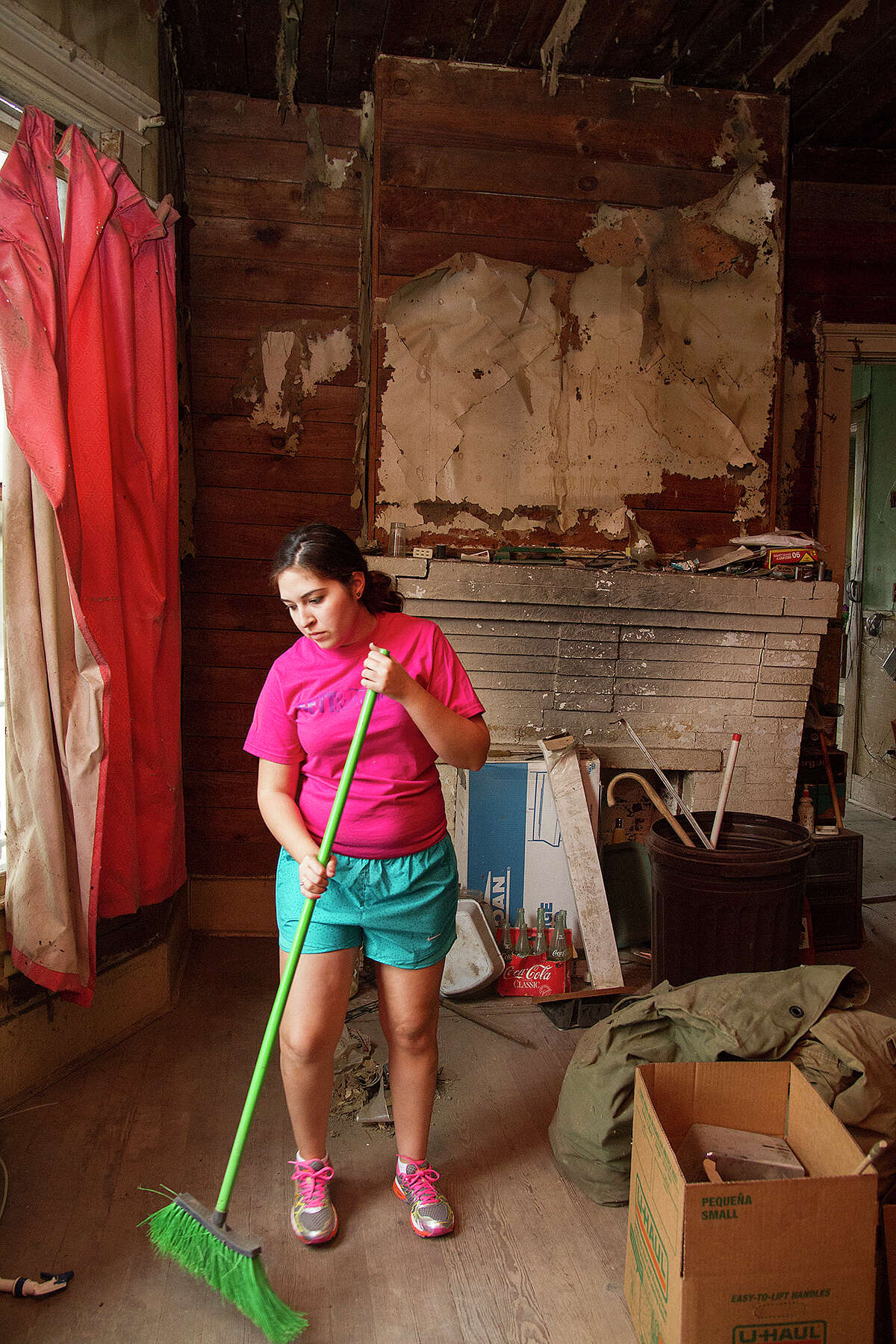 Megan Lenz helps clean up Miguel Calzada's home, Saturday, Dec. 13, 2014 so they can move forward with renovations.