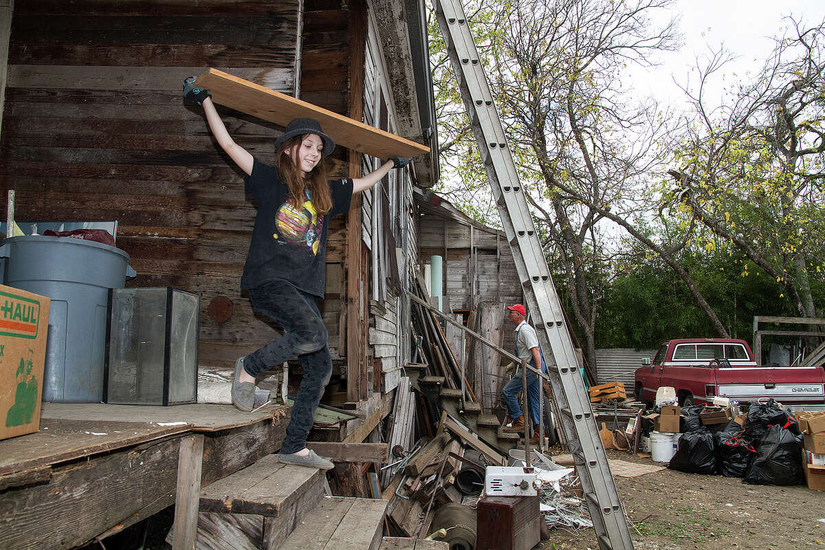 Neveah Wright, 10, volunteers her time cleaning out Miguel Calzada's home in Beacon Hill, Saturday, Dec. 13, 2014.