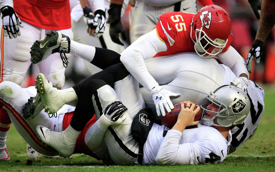 Kansas City's Tamba Hali (No. 55) brings down Raiders quarterback Derek Carr in the second half. Carr was sacked four times Sunday after his team had allowed only 20 in the first 12 games. Photo: Jamie Squire / Getty Images / 2014 Getty Images