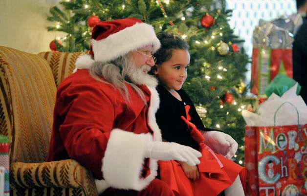 Tatiana Turner, 3, of Troy poses for a photo with Santa at the Brunch with Santa event at the Holiday Inn Express and Suites on Sunday, Dec. 14, 2014, in Latham, N.Y.  The event is put on by Big Crunch Media with sponsors Saratoga Sweets and JM Jewelers.  This was the second year of the annual event.  (Paul Buckowski / Times Union) Photo: Paul Buckowski / 00029852A