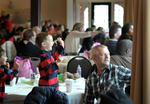 Elijah McCarty, left, 3, of Latham is excited as he sees Santa arrive outside at the Brunch with Santa event at the Holiday Inn Express and Suites on Sunday, Dec. 14, 2014, in Latham, N.Y.   McCarty is sitting with his grandfather, Dan McCarty of Greenfield Center.  The event is put on by Big Crunch Media with sponsors Saratoga Sweets and JM Jewelers.  This was the second year of the annual event.  (Paul Buckowski / Times Union) Photo: Paul Buckowski / 00029852A