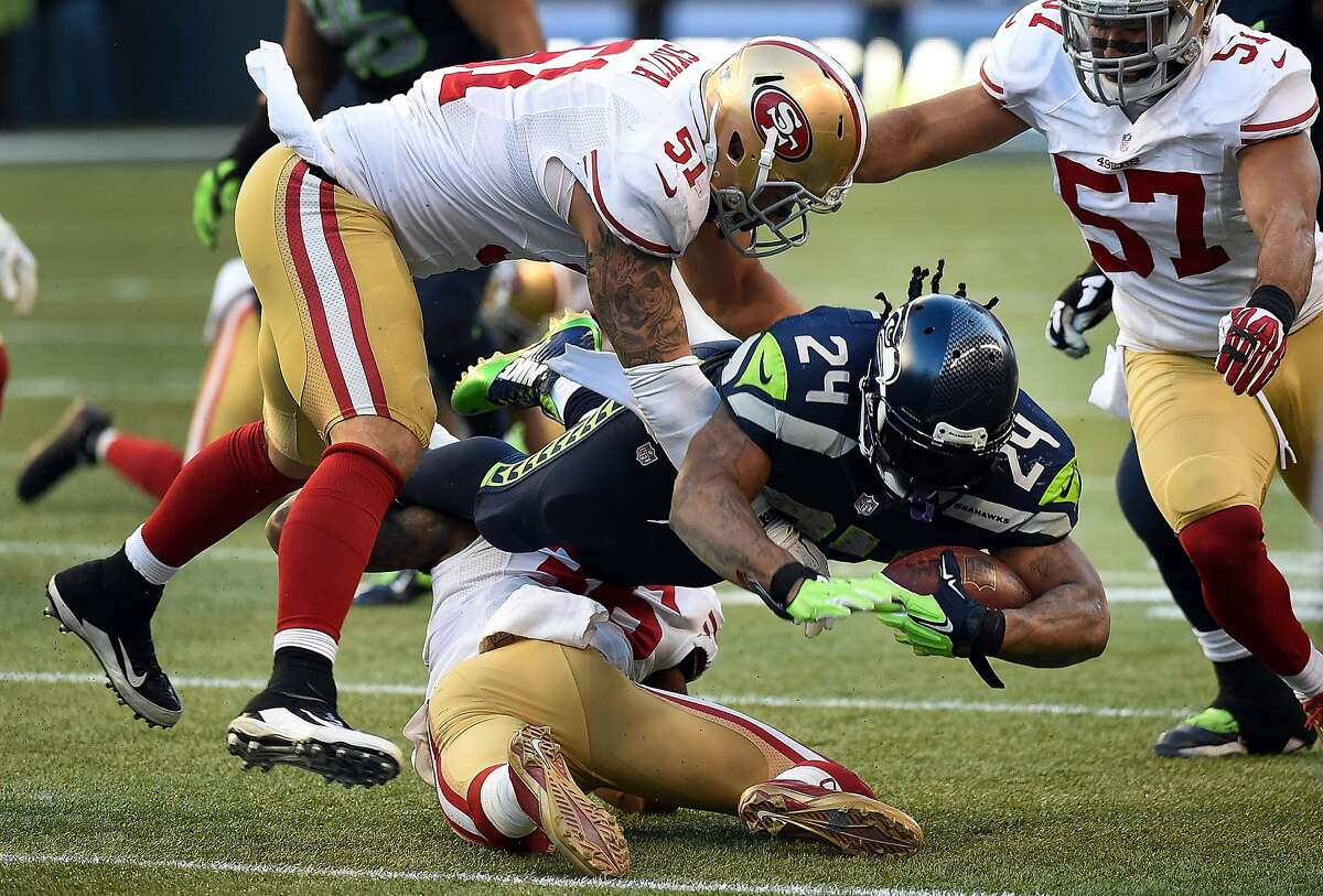 SEATTLE, WA - DECEMBER 14: Running back Marshawn Lynch #24 of the Seattle Seahawks dives forward with the ball as outside linebacker Dan Skuta #51 of the San Francisco 49ers and inside linebacker Michael Wilhoite #57 of the San Francisco 49ers close in during the third quarter of the game at CenturyLink Field on December 14, 2014 in Seattle, Washington. (Photo by Steve Dykes/Getty Images)