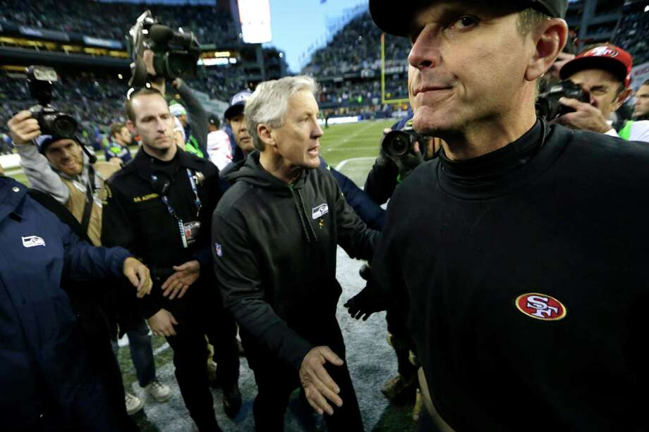 San Francisco 49ers head coach Jim Harbaugh, right, shakes hands with Seattle Seahawks head coach Pete Carroll, center, after an NFL football game, Sunday, Dec. 14, 2014, in Seattle. The Seahawks won 17-7. (AP Photo/John Froschauer) Photo: John Froschauer / Associated Press / FR74207 AP