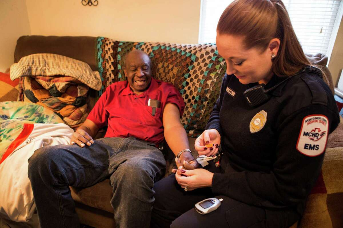 """Paramedic Nivea Wheat does a blood sugar test on William Jones at his Conroe home on Wednesday. """"Community Paramedicine,"""" a new Montgomery County Hospital District program, has paramedics proactively go out into the community to help recurring 911 users with a range of issues."""