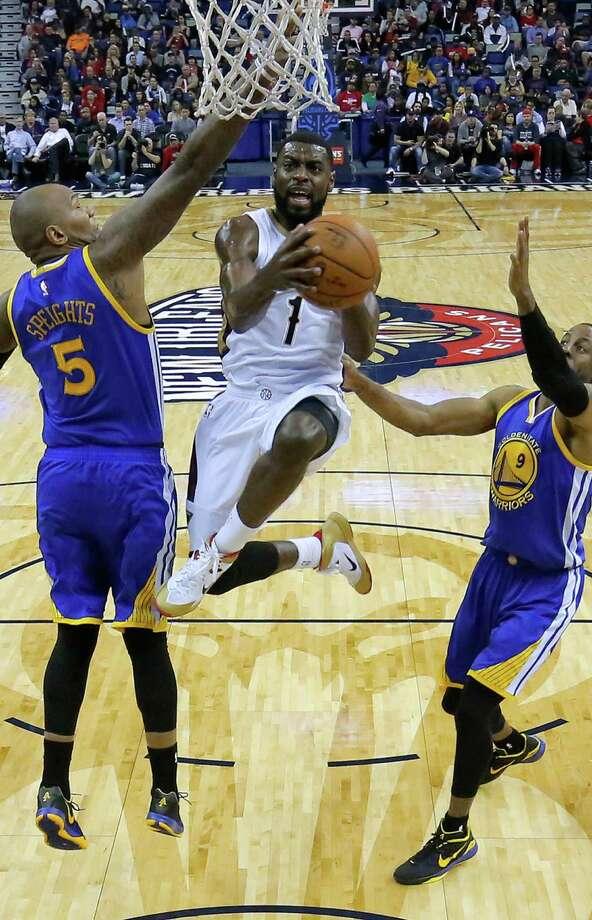 Pelicans forward Tyreke Evans drives between Warriors forward Marreese Speights (5) and guard Andre Iguodala in New Orleans. Photo: Jonathan Bachman / Associated Press / FR170615 AP