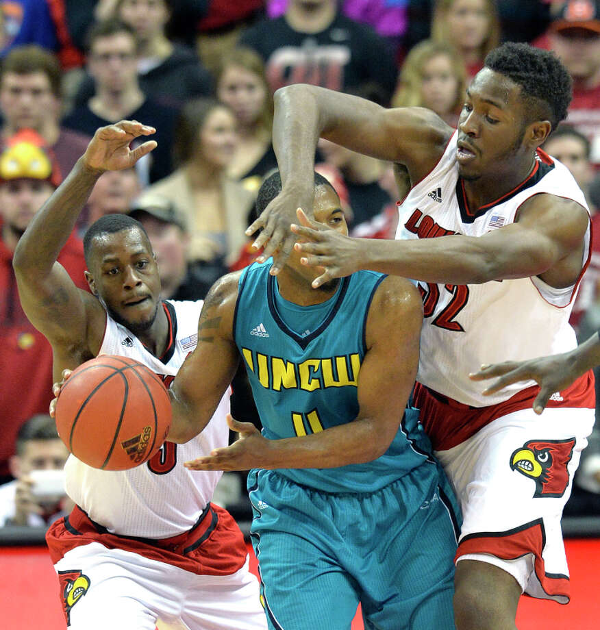 Louisville's Chris Jones (left) and Chinanu Onuaku smother UNC Wilmington's Jordan Talley. Photo: Timothy D. Easley / Associated Press / FR43398 AP