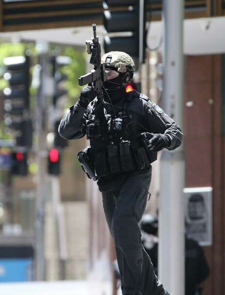 A police officer runs along a street close to a cafe under siege in the central business district of Sydney, Australia, on Monday. Television footage showed several people in the cafe with their arms in the air.  Photo: Rob Griffith, STF / AP