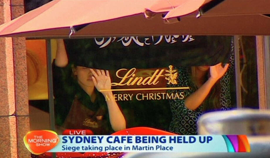 People hold up a flag with Arabic writing in a Sydney cafe where a gunman took hostages. Photo: Associated Press / Channel 7 via AP Video