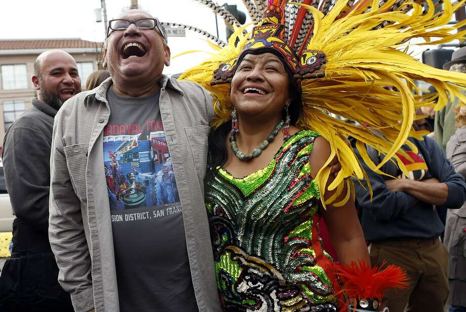 Mural artist Daniel Galvez and traditional Aztec dancer Connie Rivera share a light moment during the Carnaval Mural restoration celebration on 24th Street and Van Ness in the Mission District of San Francisco, Calif., on Sunday, December 14, 2014. Photo: Scott Strazzante, The Chronicle