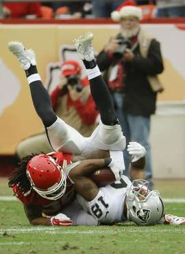 Kansas City Chiefs defensive back Jamell Fleming (30) tackles Oakland Raiders wide receiver Andre Holmes (18) during the second half of an NFL football game in Kansas City, Mo., Sunday, Dec. 14, 2014. (AP Photo/Charlie Riedel)