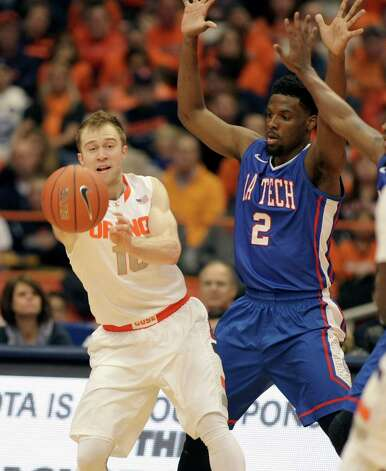 Syracuse's Trevor Cooney, left, passes the ball under pressure from Louisiana Tech's Erik McCree, right, in the first half an NCAA college basketball game in Syracuse, N.Y., Sunday, Dec. 14, 2014. (AP Photo/Nick Lisi) ORG XMIT: NYNL103 Photo: Nick Lisi / FR171024 AP