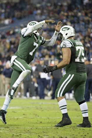 NASHVILLE, TN - DECEMBER 14:   Geno Smith #7 jumps into the arms of Oday Aboushi #75 of the New York Jets after a touchdown in the fourth quarter of a game against the Tennessee Titans at LP Field on December 14, 2014 in Nashville, Tennessee.  The Jets defeated the Titans 16-11.  (Photo by Wesley Hitt/Getty Images) ORG XMIT: 507883557 Photo: Wesley Hitt / 2014 Getty Images