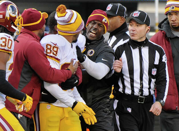 Washington Redskins wide receiver Santana Moss (89) is held back by teammates as he argues with a referee at the end of the first half against the New York Giants during an NFL football game, Sunday, Dec. 14, 2014, in East Rutherford, N.J. (AP Photo/Bill Kostroun)  ORG XMIT: ERU115 Photo: Bill Kostroun / FR51951 AP