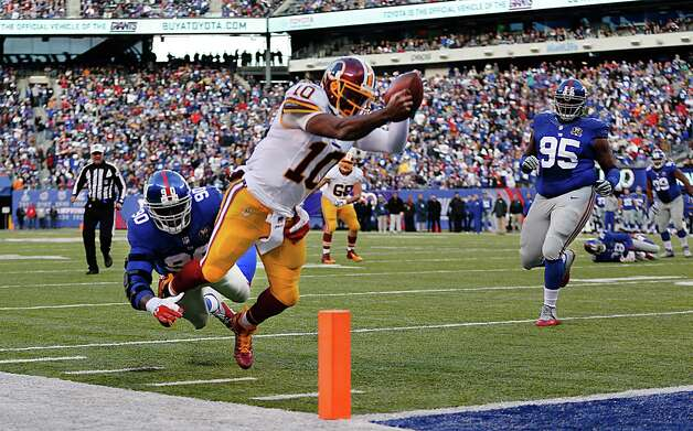 Washington Redskins quarterback Robert Griffin III (10) leaps for the goal line attempting to score a touchdown against New York Giants defensive end Jason Pierre-Paul (90) during the second quarter of an NFL football game, Sunday, Dec. 14, 2014, in East Rutherford, N.J. (AP Photo/Julio Cortez)  ORG XMIT: ERU114 Photo: Julio Cortez / AP