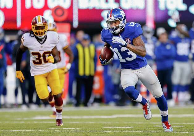 New York Giants wide receiver Odell Beckham (13) takes the ball for a touchdown as Washington Redskins free safety E.J. Biggers (30) pursues during the third quarter of an NFL football game, Sunday, Dec. 14, 2014, in East Rutherford, N.J. (AP Photo/Julio Cortez)  ORG XMIT: ERU126 Photo: Julio Cortez / AP