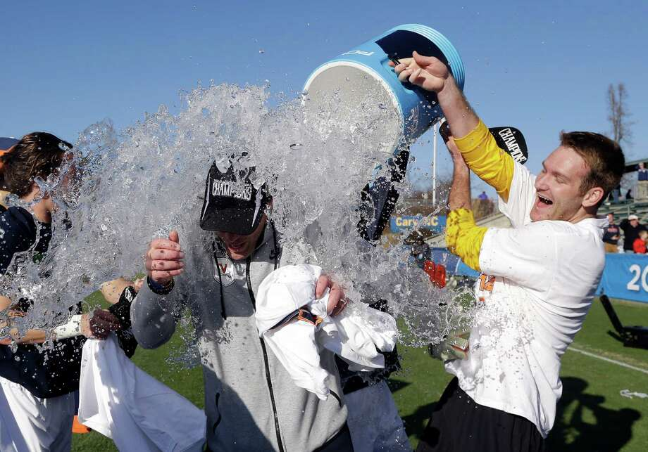 Virginia men's soccer coach George Gelnovatch receives a national championship-caliber soaking after the Cavaliers' victory over UCLA. Photo: Gerry Broome, STF / AP