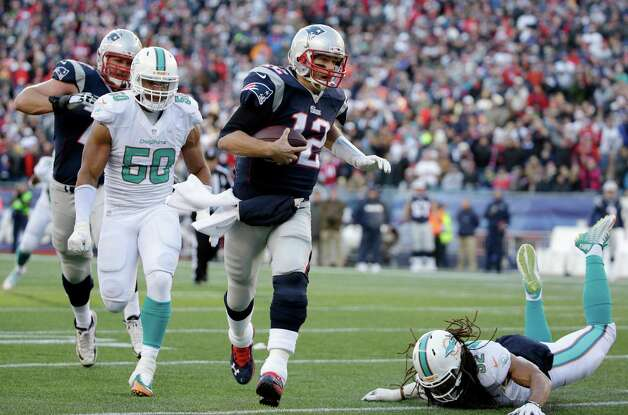 New England Patriots quarterback Tom Brady (12) runs with the ball as Miami Dolphins defensive end Olivier Vernon (50) gives chase in the second half of an NFL football game, Sunday, Dec. 14, 2014, in Foxborough, Mass. (AP Photo/Steven Senne) ORG XMIT: FBO120 Photo: Steven Senne / AP