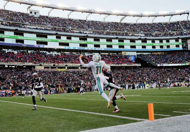 Miami Dolphins wide receiver Mike Wallace (11) catches a touchdown pass in front of New England Patriots defensive back Malcolm Butler, right rear, and safety Devin McCourty (32) in the first half of an NFL football game, Sunday, Dec. 14, 2014, in Foxborough, Mass. (AP Photo/Charles Krupa) ORG XMIT: FBO117 Photo: Charles Krupa / AP