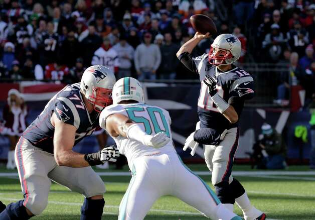 New England Patriots quarterback Tom Brady (12) passes over Miami Dolphins defensive end Olivier Vernon (50) in the first half of an NFL football game Sunday, Dec. 14, 2014, in Foxborough, Mass. (AP Photo/Charles Krupa) ORG XMIT: FBO105 Photo: Charles Krupa / AP