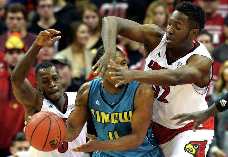 Louisville's Chinanu Onuaku, right, gets his hands in the face of UNC Wilmington's Jordan Talley as Louisville's Chris Jones, left, assists during the second half of an NCAA college basketball game Sunday, Dec. 14, 2014, in Louisville, Ky. Louisville won 68-57. (AP Photo/Timothy D. Easley) ORG XMIT: KYTE205 Photo: Timothy D. Easley / FR43398 AP